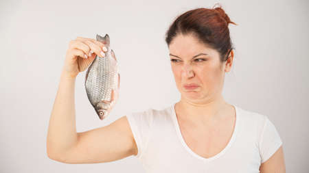 Caucasian woman opposes the disgusting smell of fish. A metaphor for womens health and intimate hygiene.