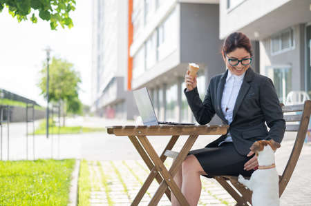 Business woman works on a laptop plays with a puppy of Jack Russell Terrier in a summer cafe. A small dog stands on its hind paws and begs for ice cream from the owner on the street 스톡 콘텐츠