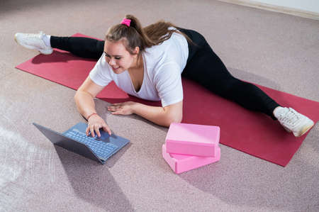 Young caucasian fat woman doing bends on a sports mat and watching a training video on a laptop. A chubby girl stretches the split remotely using video communication