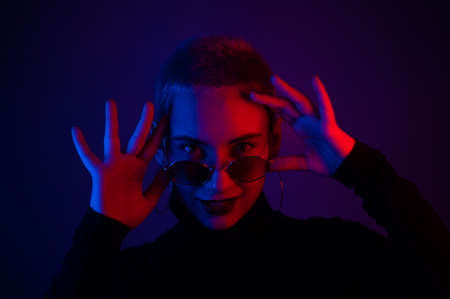 Portrait of a beautiful young woman with short hair in sunglasses in neon light 스톡 콘텐츠