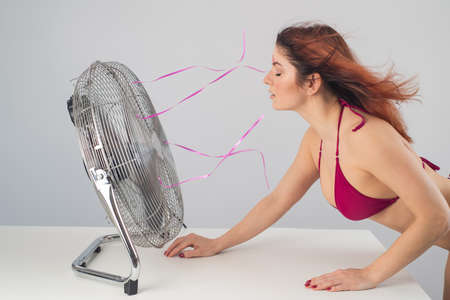 Red-haired Caucasian woman in bikini enjoys cold airflow from electric fan against white background. Climate control on a hot summer day 스톡 콘텐츠