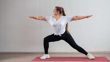 Young fat woman doing flexibility exercises on a white background Standard-Bild