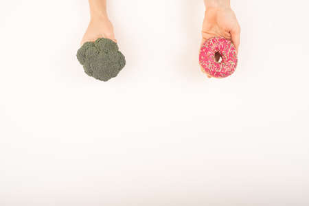 Comparison of eating habits. Woman holding broccoli and donut on a white background