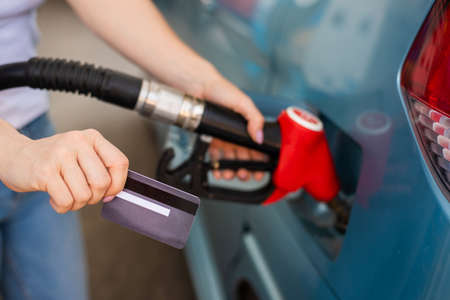 A woman fills her car with gasoline at a self-service gas station and holds a credit card 写真素材