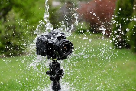 Splashes are flying into a digital camera on a tripod.