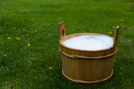 Wooden tub with foam on a green lawn in the countryside 写真素材