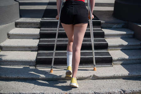 Young woman with ankle injury climbs stairs on crutches. 写真素材