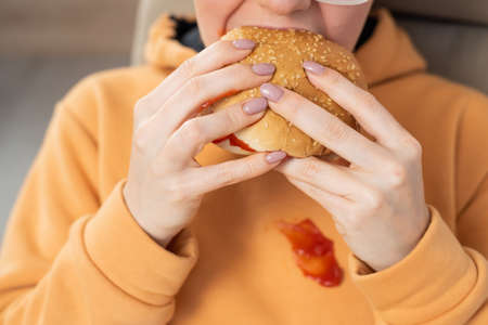 Caucasian young woman eating burger and getting dirty in ketchup. Sloppy girl