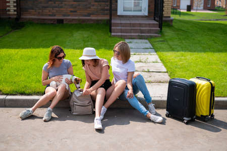 Three Caucasian women and a dog go on a trip. The girls are sitting on the curb with suitcases and waiting for a taxi. Summer vacation concept together with girlfriends