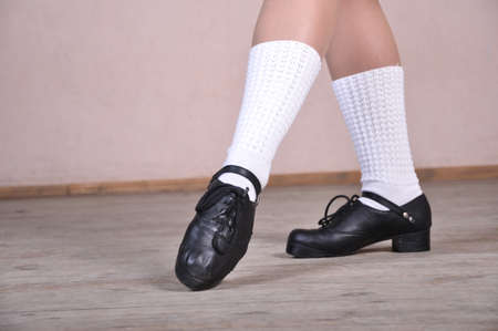 Close-up of female legs in black leather shoes dancing national Irish dances.