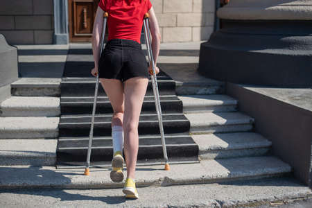 Young woman with ankle injury climbs stairs on crutches. Banque d'images