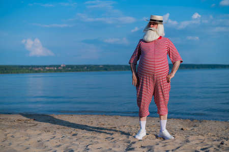 An elderly man in a striped retro swim suit and Boater on the seashore 写真素材