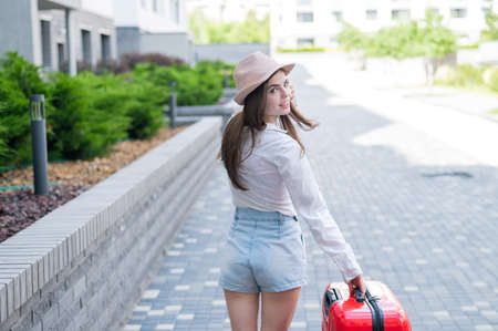 Young caucasian woman in a hat and shorts stands on the street with a red suitcase. 写真素材