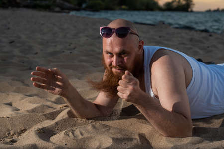A humorous portrait of a brutal man in a T-shirt and boxers on the beach at sunset 写真素材