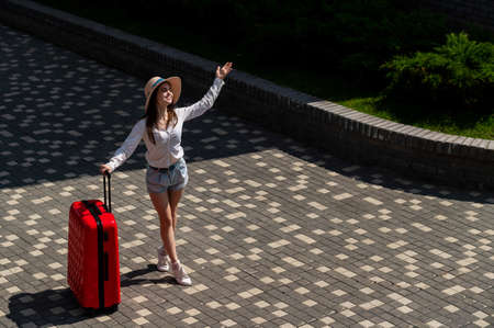 Happy caucasian young woman in hat and shorts holding a large red suitcase outdoors. 写真素材