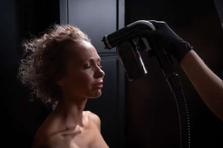 A master applies tinting paint to the face of a Caucasian woman. Instant tanning procedure 写真素材