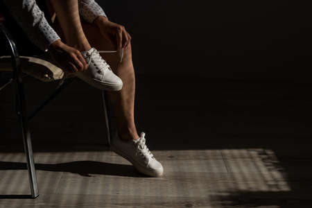 Woman put on new white leather sneakers 写真素材