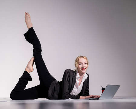 Barefoot ballerina dressed in a business suit poses for a laptop and drinks coffee. Flexible woman works at the computer 写真素材