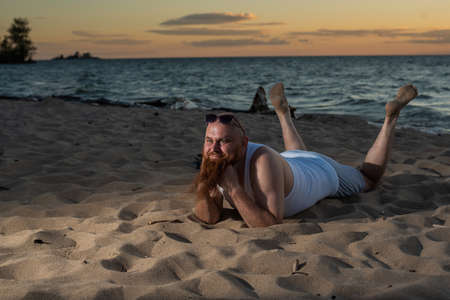 Funny bald man with red beard posing on the beach at sunset. A humorous male parody of a glamorous girl.