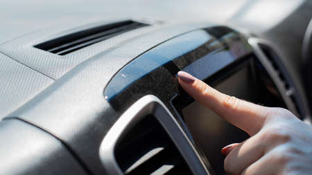 Wipe dust off car dashboard with finger.