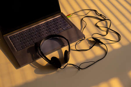 Headphones lie on a laptop keyboard on a white table. The shadow from the blinds falls on the desktop.
