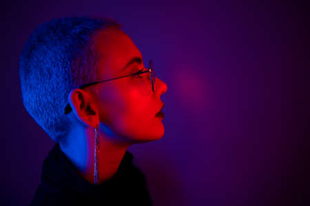 Portrait of beautiful young woman with short hair wearing glasses in neon light