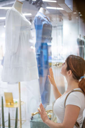 Caucasian woman looking at a shop window and dreaming about a dress.