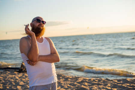 Brutal bearded man smokes a cigarette on the beach. Bad habit leads to cancer