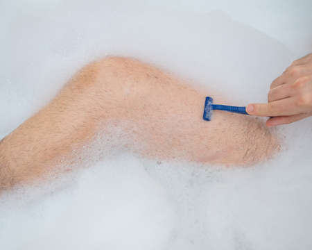 Funny picture of a man taking a relaxing bath and shaving his legs. Close-up of male feet in a bubble bath. Top view.