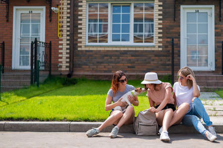 Three Caucasian women and a dog go on a trip. The girls are sitting on the curb with suitcases and waiting for a taxi. Summer vacation concept together with girlfriends Stock fotó