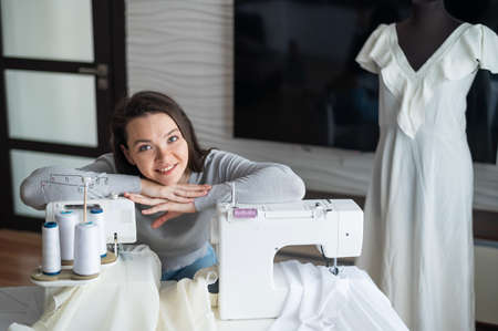 Young caucasian woman sews at home