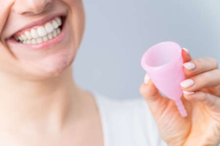 Close-up portrait of smiling Caucasian woman holding pink menstrual cup on white background. Alternative to tampons and pads on critical days. Stockfoto
