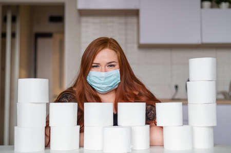 Woman wearing medical mask and holding several rolls of toilet paper.