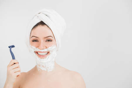 Cheerful caucasian woman with a towel on her head and shaving foam on her face holds a razor on a white background