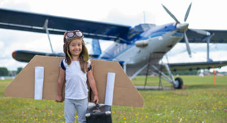 A little girl in a pilots costume holds a retro suitcase in the field near the plane with a propeller. A child in a hat with glasses and cardboard wings dreams of flying in the sky Stockfoto