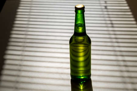 Green glass beer bottle in the shade of the blinds. Stockfoto