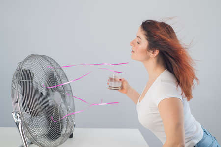 A red-haired Caucasian woman chills by the electric fan and drinks a cold drink. Climate control in the apartment Stockfoto