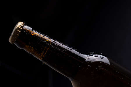 Dark glass beer bottle with condensation drops on black background.
