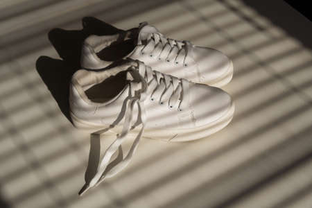 Close-up of womens white leather sneakers in the shade of the blinds.