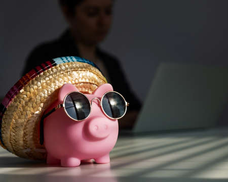 Piggy bank in sunglasses and a sombrero in the background woman works for a laptop. Stockfoto