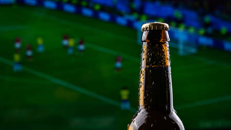 A bottle of beer on the background of a broadcast of a football match. Stockfoto
