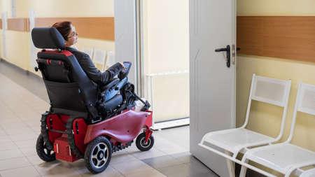 Caucasian woman in electric wheelchair in hospital corridor.