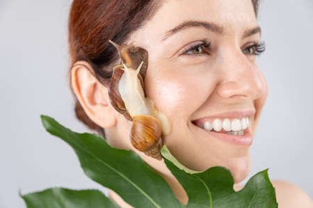 Beautiful caucasian smiling woman with snails on her face. Skin rejuvenation therapy.