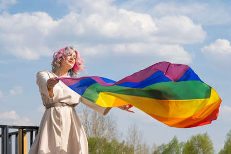 Caucasian woman with curly colored hair holding lgbt flag. Lesbian woman holding a rainbow flag outdoors Stockfoto