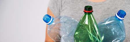 Close-up of female hand holding green plastic bottle on white background. Stockfoto