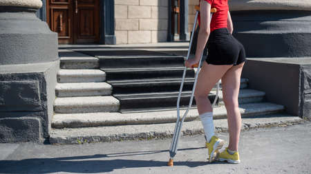 Young woman with ankle injury climbs stairs on crutches. Stockfoto