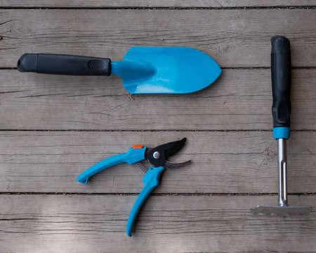 Small blue spatula, garden pruner and rake on the wooden floor. Gardeners tools