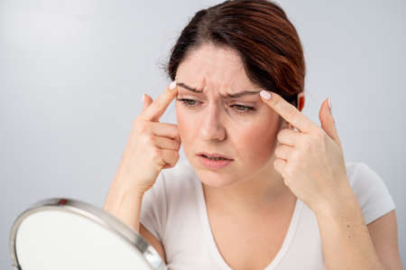 Caucasian woman looks at herself in the mirror and is upset because of facial wrinkles on her face.
