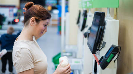 Caucasian woman uses a self-checkout counter. Self-purchase of groceries in the supermarket without a seller Stockfoto