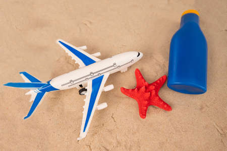 Airplane model red starfish and a tube of sunscreen on the sand. seaside holiday concept.